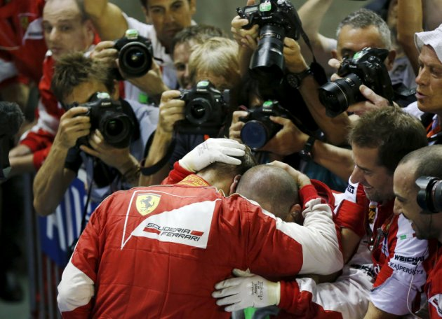 Ferrari Formula One driver Vettel of Germany hugs his team mates after winning the Singapore F1 Grand Prix
